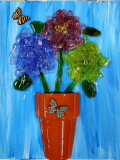 Terra cotta flower pot with shattered glass and wooden butterflies